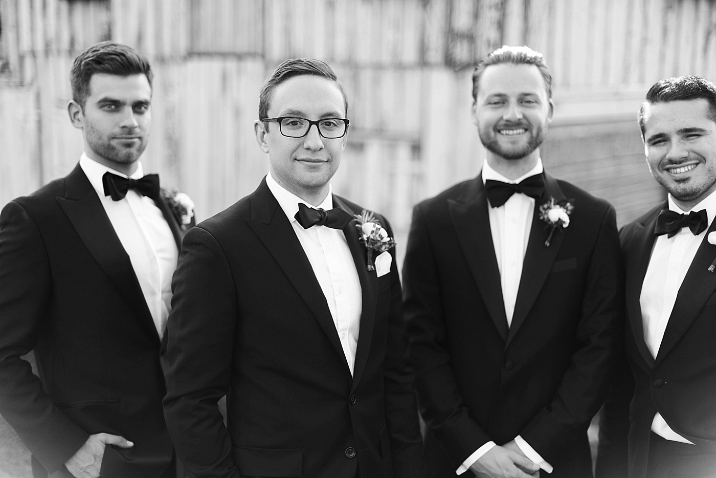 groom and his groomsmen posing in front of a barn